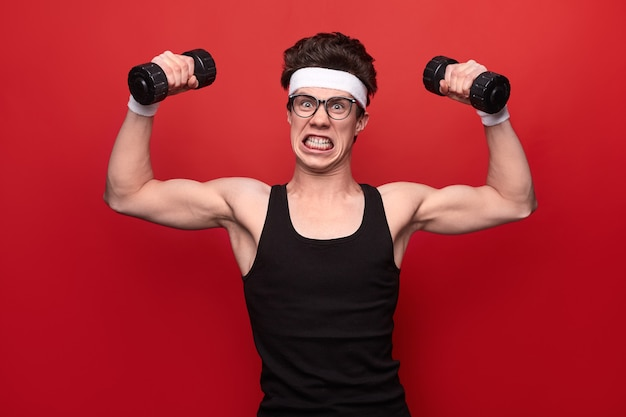 Funny young male geek in glasses lifting dumbbells and looking at camera against red background