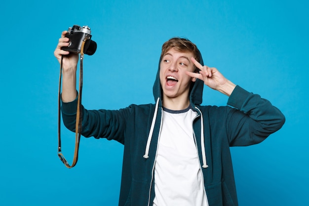 Funny young man in casual clothes doing selfie shot on retro vintage photo camera showing victiry sign isolated on blue wall . people sincere emotions, lifestyle concept.