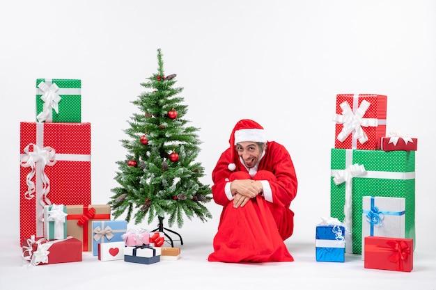 贈り物と白い背景の上の地面に座って飾られたクリスマスツリーでサンタクロースに扮した面白い若い男