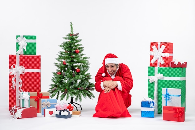 Funny young man dressed as santa claus with gifts and decorated christmas tree sitting on the ground on white background