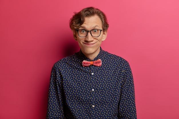 Il giovane divertente guarda con espressione comica, indossa occhiali da vista e camicia elegante, nota qualcosa di interessante, ha una conversazione piacevole con l'interlocutore, isolato su un muro rosa