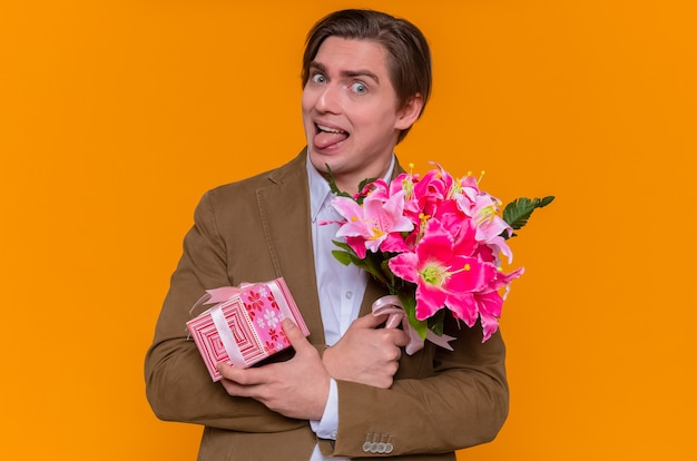 Giovane divertente che tiene presente e bouquet di fiori guardando la parte anteriore che attacca fuori la lingua andando a congratularsi con la giornata internazionale della donna in piedi sopra la parete arancione