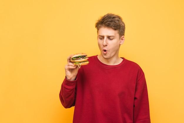 面白い若い男が彼の手でハンバーガーを保持