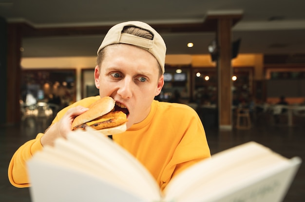 帽子をかぶった面白い若い男がサンドイッチを噛んで焦点を当てた本を読む