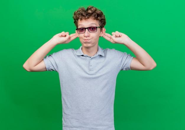 녹색 벽 위에 그의 귀를 blowiong 뺨을 행복하고 쾌활한 서 보여주는 회색 폴로 셔츠를 입고 검은 안경에 재미 젊은 남자