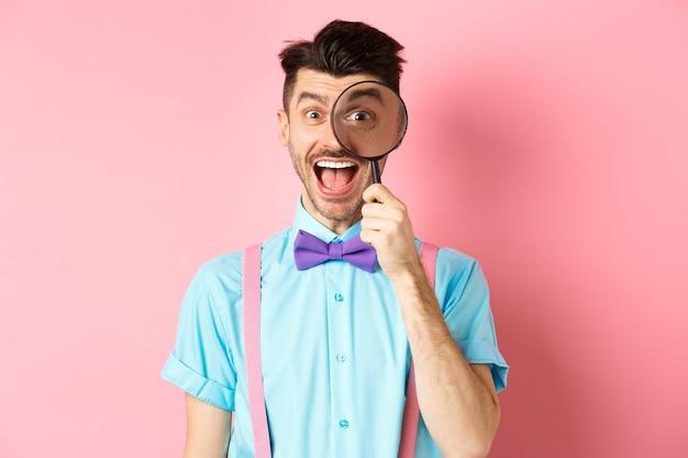 蝶ネクタイの面白い若い男は、虫眼鏡を通して見て、舌を見せて、幸せそうに笑って、ピンクを楽しんでいます。