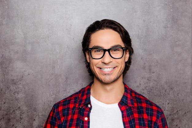 Забавный молодой человек в очках, показывая свою белую улыбку