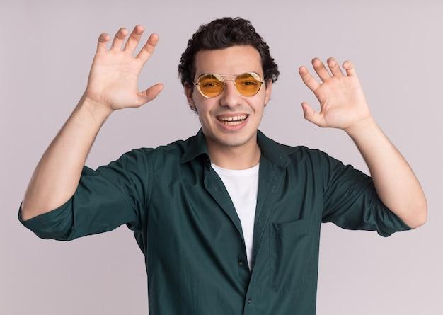 흰 벽 위에 서있는 고양이로 앞 발톱 제스처를 만드는 안경을 쓰고 녹색 셔츠에 재미있는 젊은 남자