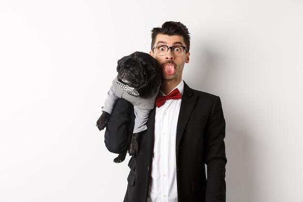 Забавный молодой человек в костюме вечеринки, показывающий язык и держащий милого черного мопса на плече, празднует с домашним животным, стоя над белым.