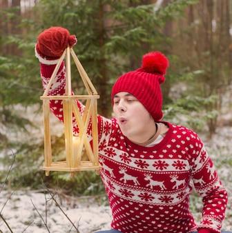 Забавный молодой человек в красной шляпе в зимнем лесу