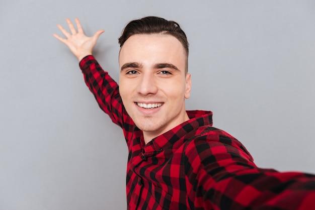 Забавный молодой человек в рубашке, делая селфи и позирует с рукой на фоне.