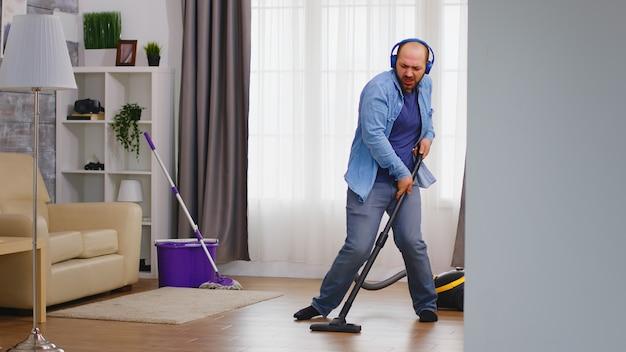 Забавный молодой человек слушает музыку в наушниках во время уборки пола пылесосом