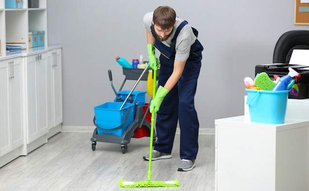 Funny young man moping floor in office