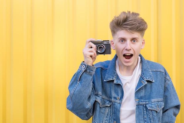 レトロなカメラを撮影して、カメラに探している面白いの若い男。
