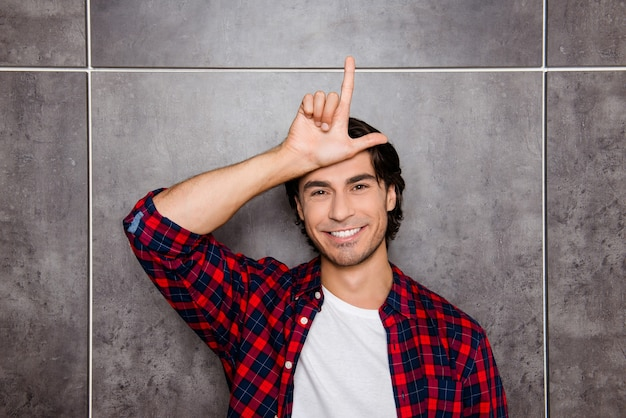Funny young man showing sign loser with fingers near forehead and ridicule of somebody