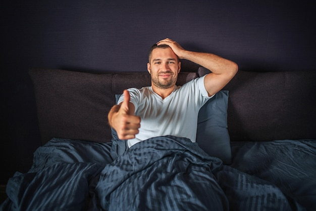 Funny young man sitting on bed and smiling. he shows big thumb up on one hand and hold another one on head. guy is satisfied and happy.
