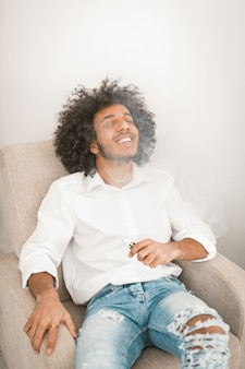Funny young man sitting and vaping electronic cigarette at home