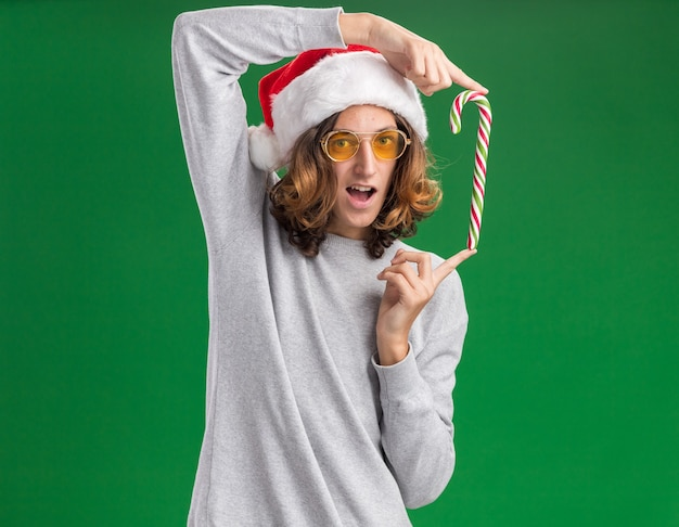 Funny young man wearing christmas santa hat and yellow glasses holding  candy cane looking at camera smiling cheerfully standing over green background
