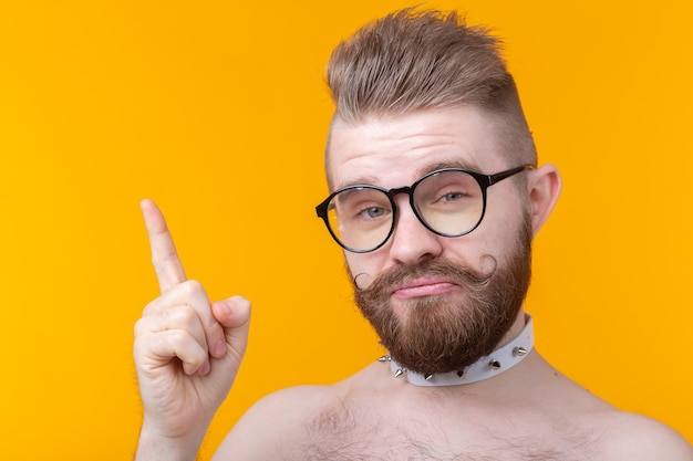 Funny young man with a mustache and a beard without a shirt and glasses shows on a yellow surface