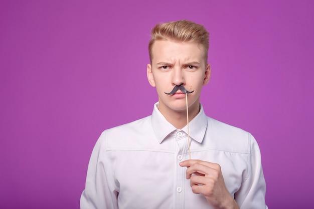 Забавный молодой человек с бумажными усами на