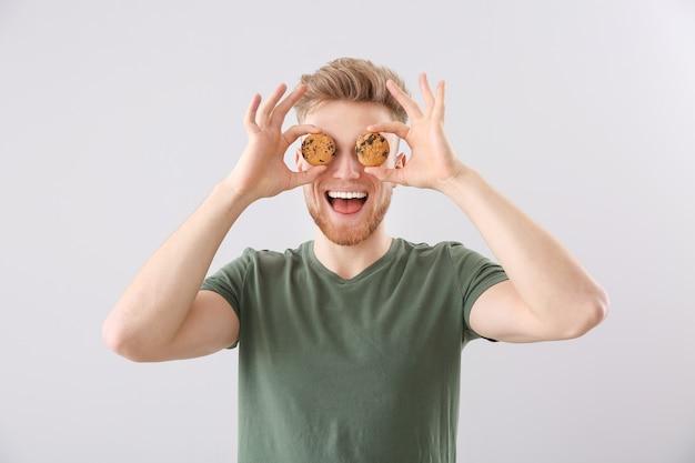 明るい背景においしいクッキーと面白い若い男