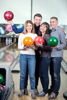 Funny young people smiling at the camera playing bowling.