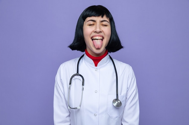 Funny young pretty caucasian girl in doctor uniform with stethoscope stucks out tongue standing with closed eyes