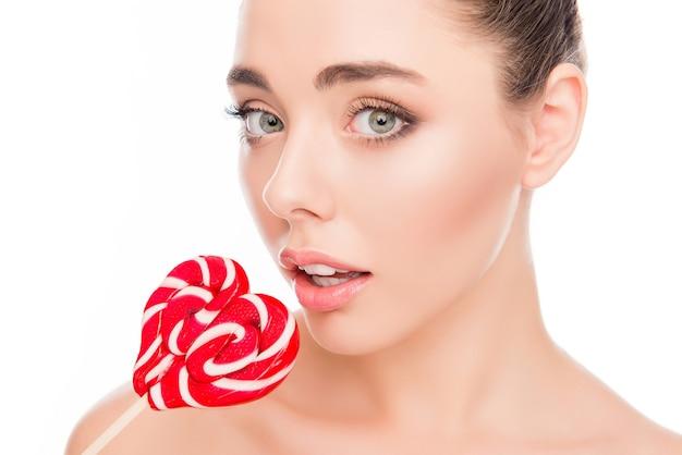 赤いロリポップを食べる面白い若いかわいい女の子