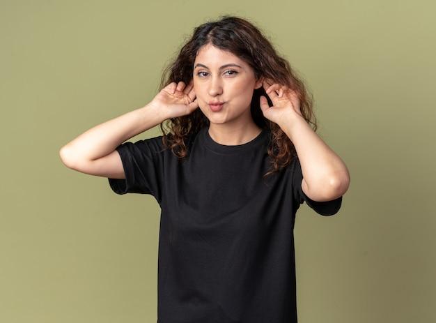 Divertente giovane ragazza carina che fa grandi orecchie con le labbra increspate isolate su un muro verde oliva