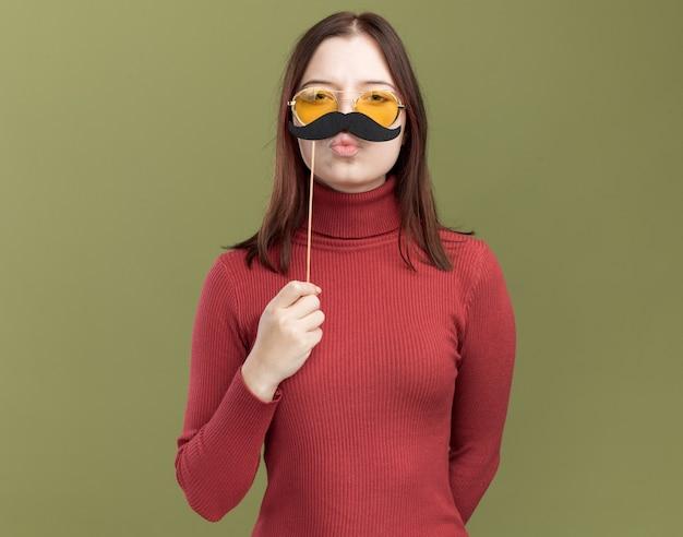 올리브 녹색 벽에 격리된 키스 제스처를 하는 입술 위의 막대기에 가짜 콧수염을 들고 등 뒤에서 손을 잡고 선글라스를 끼고 있는 재미있는 젊은 예쁜 소녀