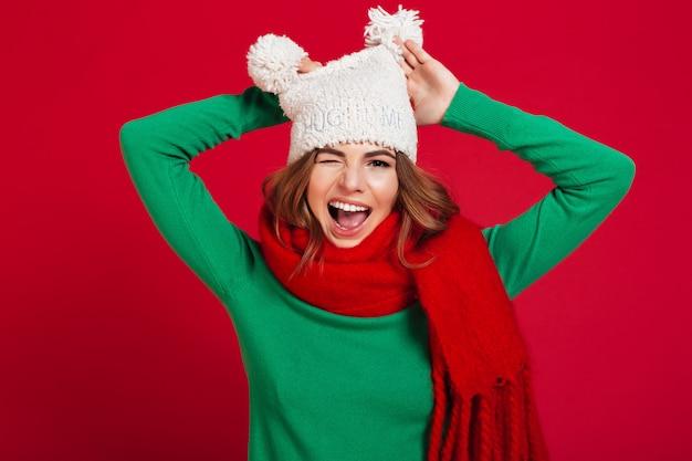 Divertente giovane bella signora che indossa cappello e sciarpa calda