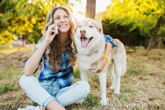 晴れた夏の日に公園で犬のハスキー犬と遊ぶ面白い若いきれいな女性
