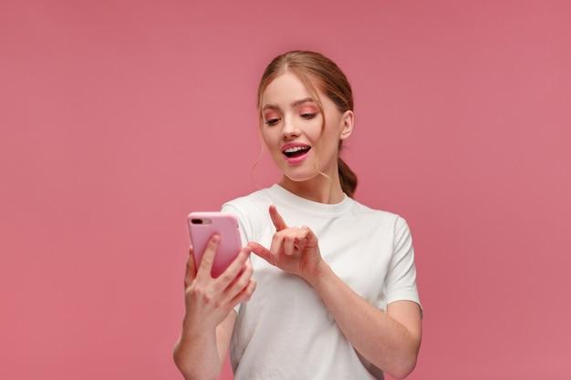 분홍색 스마트폰을 들고 웃고 있는 우스꽝스러운 젊은 빨간 머리 여자 휴대폰 앱 문자를 사용하여 웃는 행복한 소녀...