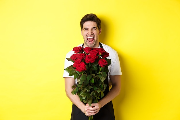 Funny young salesman in black apron holding bouquet of roses, florist laughing and standing over yellow background.
