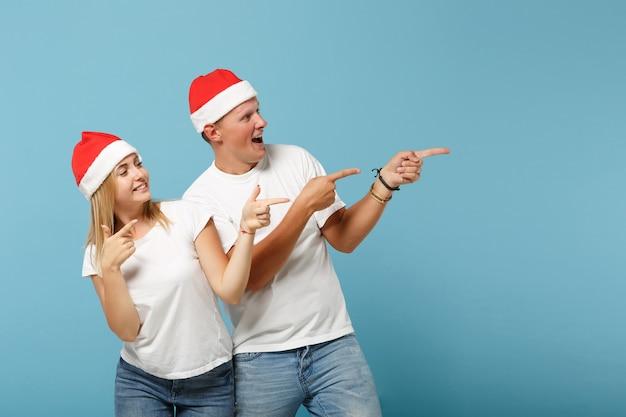 クリスマスの帽子のポーズで面白い若いサンタカップルの友人の男と女
