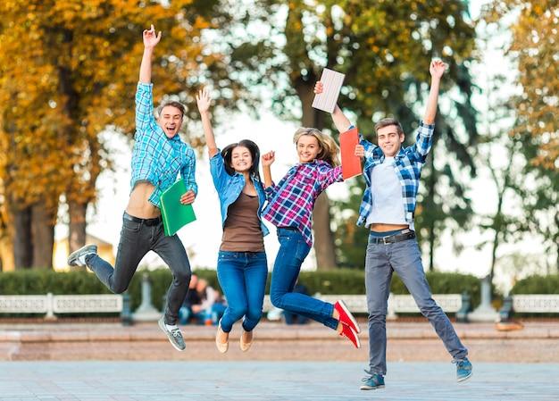 面白い若い学生が公園で一緒にジャンプしています。