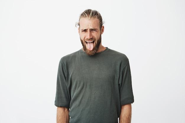 Divertente giovane svedese con acconciatura alla moda e barba sporgente lingua