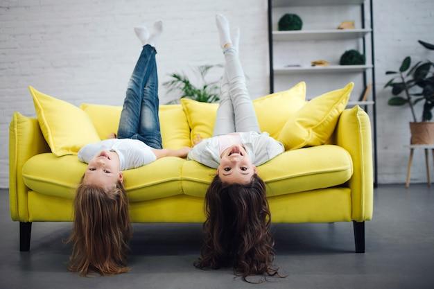 노란색 소파에 누워 및 straigt 찾고 재미 젊은 청소년. 그들은 웃어요. 여자 아이들은 다리를 공중에 hold니다. 그들의 머리 접촉 층.