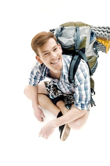 Funny young tourist is sitting with backpack on white background traveler is preparing for hike