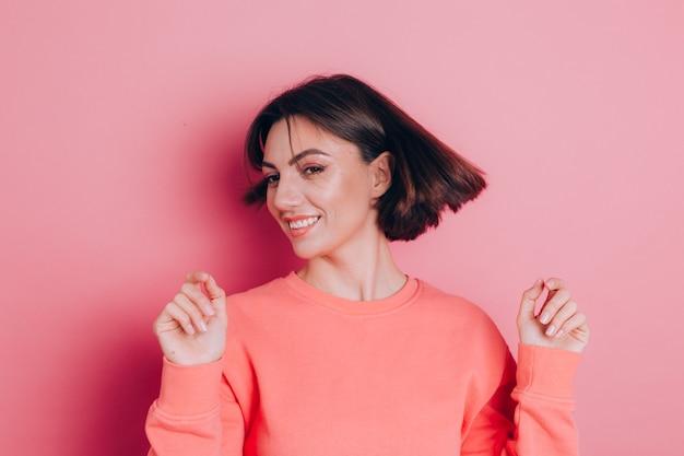 분홍색 배경 스튜디오 초상화에 고립 된 캐주얼 옷에 재미있는 젊은 여자 20 대. 사람들의 감정 라이프 스타일 개념. 흐르는 머리카락으로 머리를 흔들어