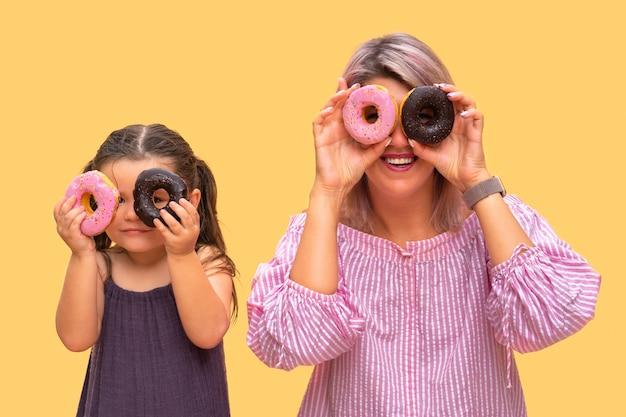 재미있는 젊은 여자와 노란색 벽 바탕에 아이. 어머니와 그녀의 딸 소녀는 화려한 도넛으로 재미 있습니다. 핑크와 초콜릿 도넛.