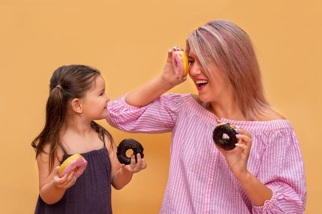 黄色の壁の背景に面白い若い女性と子供。母と娘の女の子はカラフルなドーナツを楽しんでいます。ピンクとチョコレートのドーナツ。