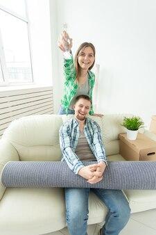 座っている間彼らの新しいアパートの鍵を手に持っている面白い若い女性と彼女の夫