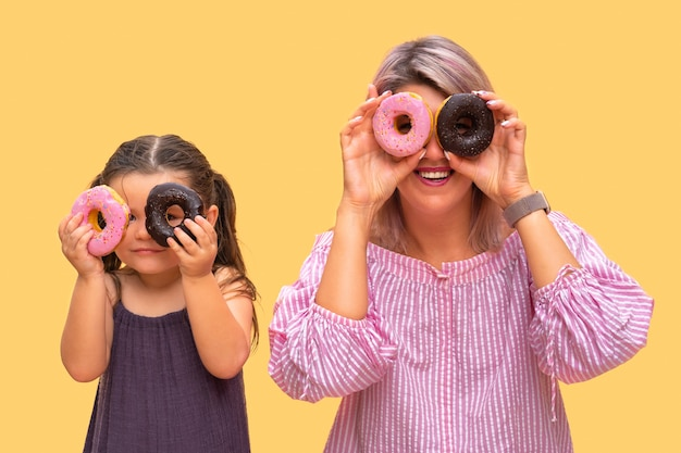 Funny young woman and child on yellow wall background. mother and her daughter girl have fun with colorful donuts. pink and chocolate donuts.