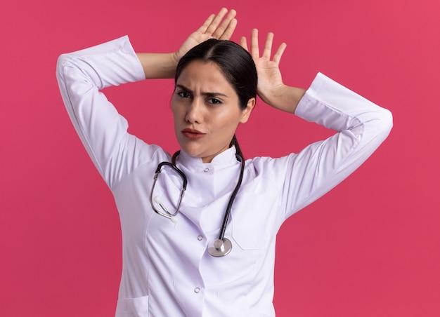청진 기 의료 코트에 재미있는 젊은 여자 의사 핑크 벽 위에 서있는 머리 위로 손으로 전면 행복하고 즐거운 모방 토끼 귀를보고