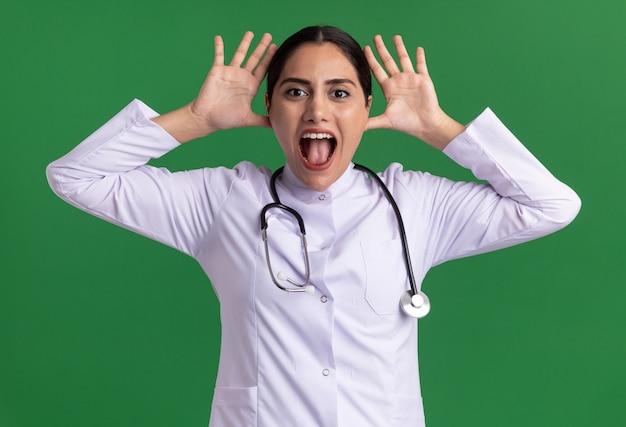 Medico divertente della giovane donna in cappotto medico con lo stetoscopio che esamina la parte anteriore che fa smorfia che attacca fuori linguetta che tiene le mani vicino alla testa che sta sopra la parete verde