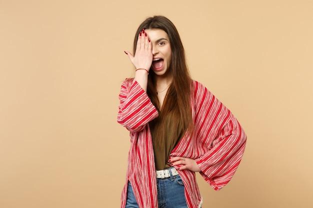 スタジオでパステルベージュの壁の背景に分離された手のひらで顔を覆って、口を大きく開いたままカジュアルな服を着た面白い若い女性。人々の誠実な感情、ライフスタイルのコンセプト。コピースペースをモックアップします。