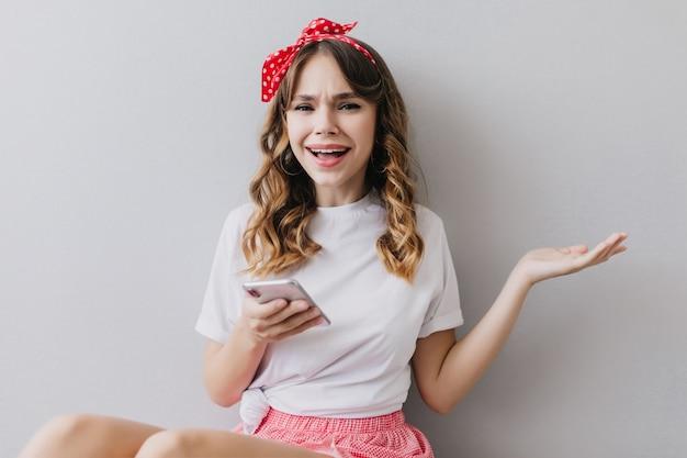電話で彼女の部屋でポーズをとってカジュアルな服装で面白い若い女性。スマートフォンを手に持っているロマンチックな白人の女の子。