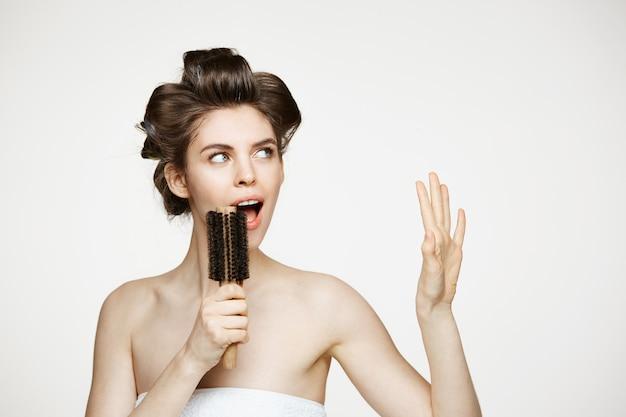 ヘアカーラーと櫛で歌う歓喜タオルで面白い若い女性。美しさとスパ。