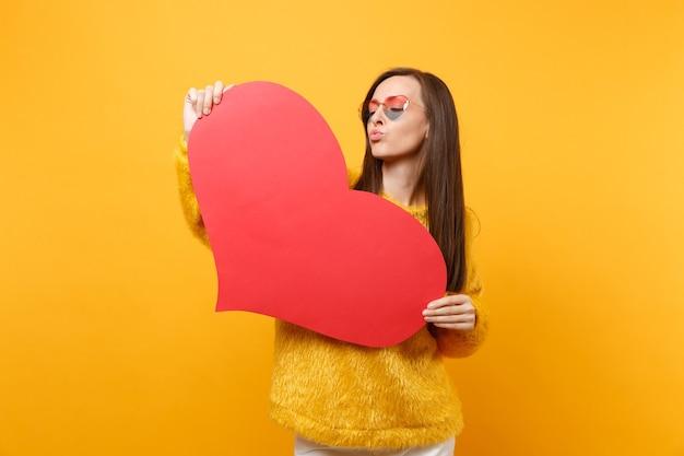 唇を吹く、空気のキスを送信し、明るい黄色の背景で隔離の空の空白の赤いハートを保持しているハートの眼鏡の面白い若い女性。人々の誠実な感情、ライフスタイルのコンセプト。広告エリア。